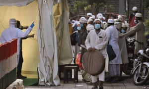 Indian paramedics screen Muslims  before they board a bus in Nizamuddin on 31 March after it emerged that dozens of attendees at a gathering earlier that month had contracted coronavirus