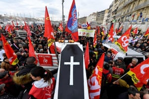 People wave the flags of French trade union General Confederation of Labour (CGT) and carry a mocked coffin as they take part in a demonstration to protest against the pension overhauls, in Marseille