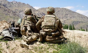 US soldiers look out over hillsides in Afghanistan.