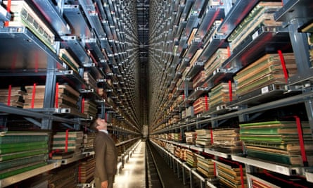 A man looks up at high shelves of archived newspapers.