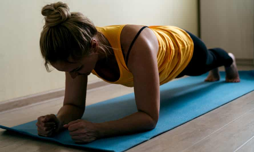 Woman on a yoga mat holding a planking pose