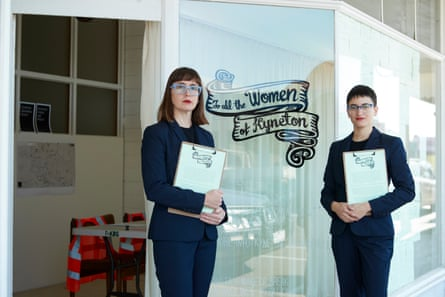 two women stand in front of a shopfront that says