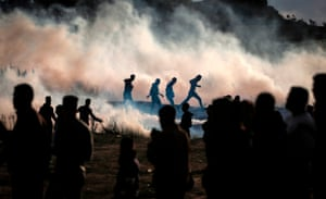 Palestinian protesters run from teargas fired by Israeli forces during a demonstration along the border with Israel.