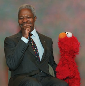 Annan laughs as he films a scene with the Muppet character Elmo during a taping of Sesame Street in December 2001 in New York