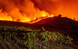 Flames approach a vineyard in northern California. Thousands of people will lose their electricity amid dangerous weather.