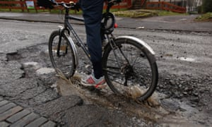 Potholes in the road with a cyclist