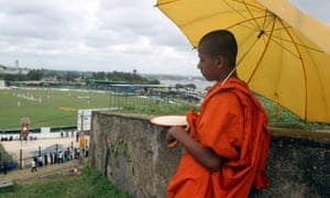 A young Sri Lankan Buddhist monk watches cricket between Sri Lanka and South Africa from the top of the old Dutch Galle fort