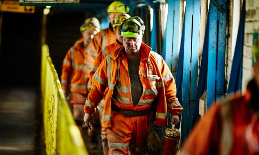 grim-faced miners leaving colliery