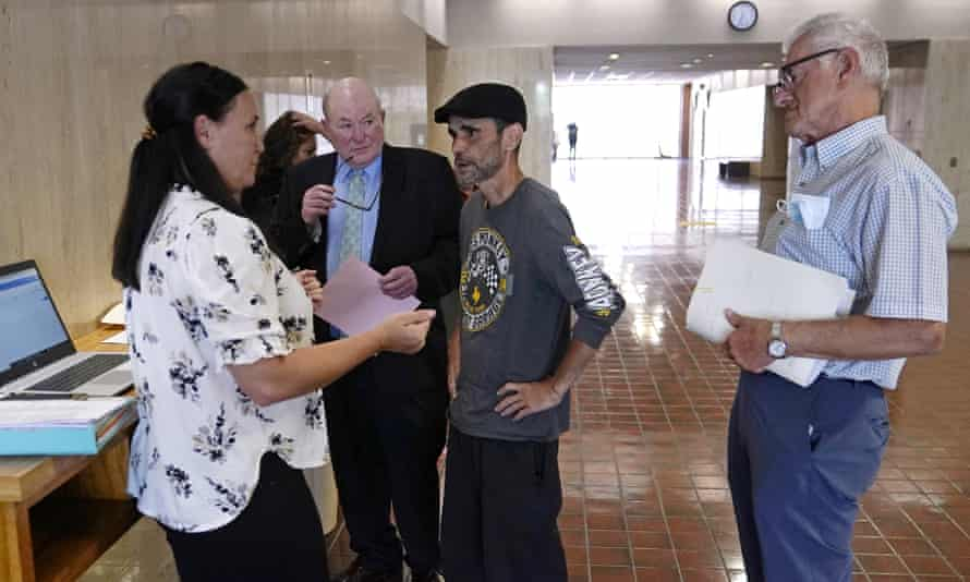 Luis Vertentes, center, speaks with a rent relief case manager ahead oof an eviction hearing in Providence, Rhode Island. 'I feel helpless, like I can't do anything even though I work and I got a full-time job,' he said.
