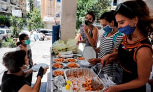 Volunteers wearing masks distribute meals to people affected by the explosion in the Ashrafieh neighbourhood of Beirut.