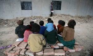 Children sitting on the ground being taught