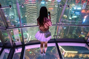 A young woman takes a picture at the Oriental Pearl Tower in Shanghai, China