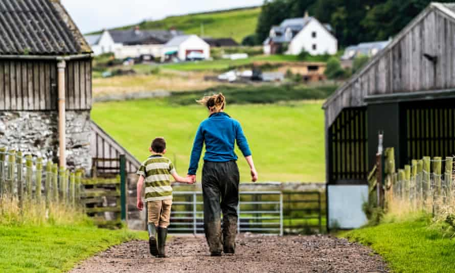 A woman and child walk on a farm near the Scottish borders, 14 August 2017.