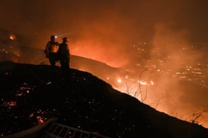 Firefighters look out over a burning hillside as they fight the Blue Ridge Fire in Yorba Linda, California, October 26, 2020.