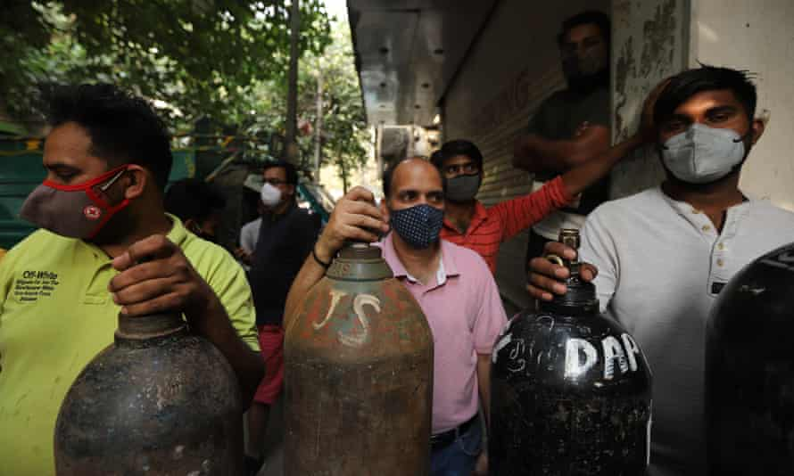 People queue with empty oxygen cylinders