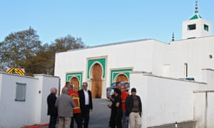 Local residents, fire and police officers stand outside the Bayonne mosque after the incident
