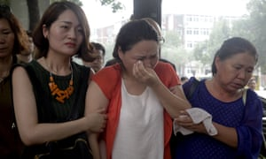 Fan Lili, center, the wife of activist Gou Hongguo, is escorted by Li Wenzu, left, the wife of imprisoned lawyer Wang Quanzhang outside the Tianjin No. 2 Intermediate People's Court in Tianjin, China.