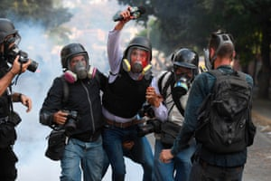 Journalist Gregory Jaimes is assisted by colleagues after being injured in a day of violent clashes on the streets of the capital.