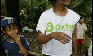 An Oxfam aid worker with children in Indonesia.