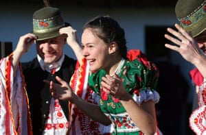 A young woman is soaked after men threw buckets of water over her in an Easter folk tradition in Mezőkövesd, Hungary