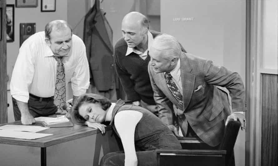 Mary Tyler Moore (as Mary Richards) sleeps on a desk. Around her are Ed Asner (as Lou Grant), Gavin MacLeod (as Murray Slaughter) and Ted Knight (as Ted Baxter).