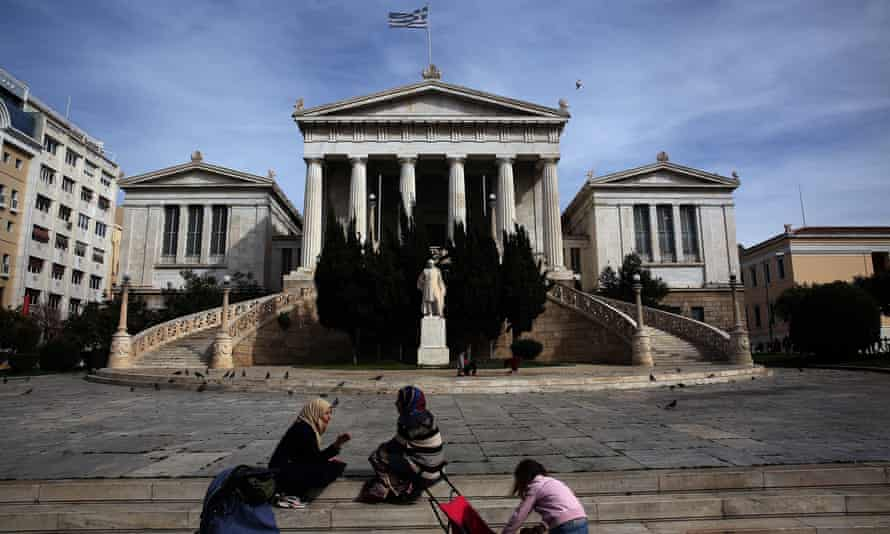 Syrian refugee women sit while their children play in front of the National Library in central Athens, Greece.