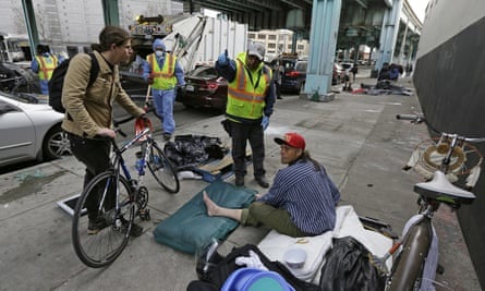 A San Francisco city worker asks a homeless man to leave the area to make room for cleaning in February 2016.