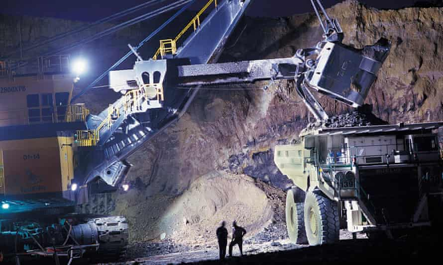 heavy machinery loads coal on to truck