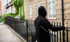 A young person wearing a hood looks down a London street with his back to the camera.
