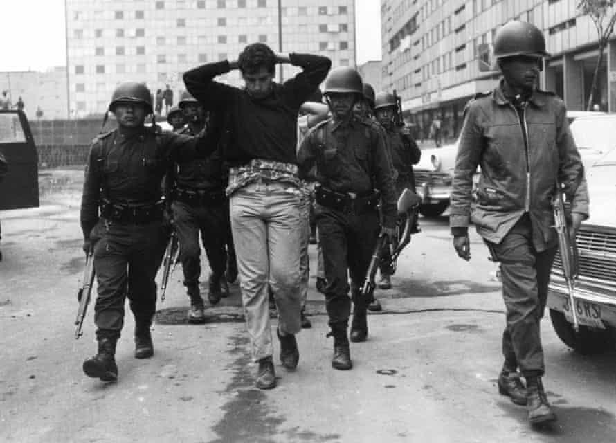 Mexican army troops escort demonstrators arrested in Mexico City the day after the massacre.