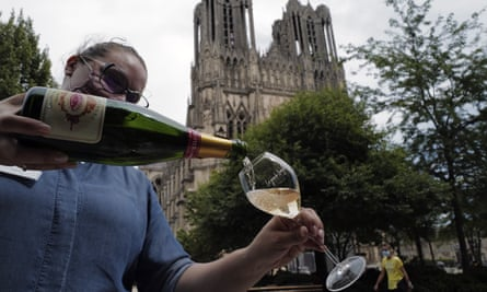 A waitress serves a glass of champagne in Reims