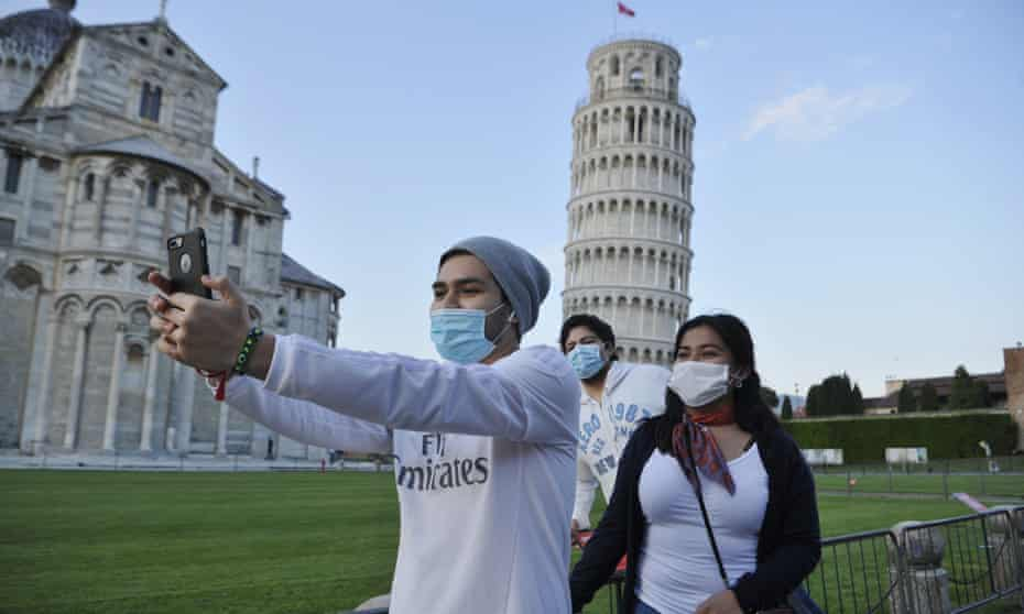 Tourists wear face masks while posing for a photograph near the Leaning Tower of Pisa, which reopened on Saturday.
