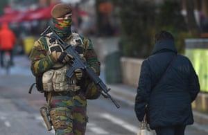 A soldier patrols Brussels in Belgium as it remains in lockdown under a maximum terror alert