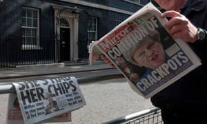 """A television cameraman outside 10 Downing Street in London on June 10, 2017, reads a copy of The Daily Mirror newspaper with the headline """"Coalition of Crackpots"""" the day after the general election."""