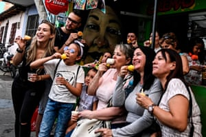 Tourists pose with ice creams, 'cremas,' during a visit to Comuna 13