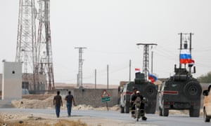Military vehicles fly Russian and Syrian national flags near the town of Manbij on Tuesday.