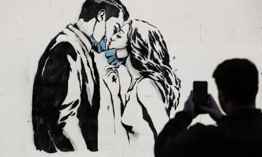Rebel Bear mural on a wall on Bank Street in Glasgow. The piece features a woman and a man pulling back to give each other a kiss.