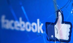 Facebook logo seen through cracked screen.