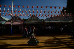 A woman walks past the striped tents of the Feria de Abril, Seville's festival of flamenco and bullfighting.