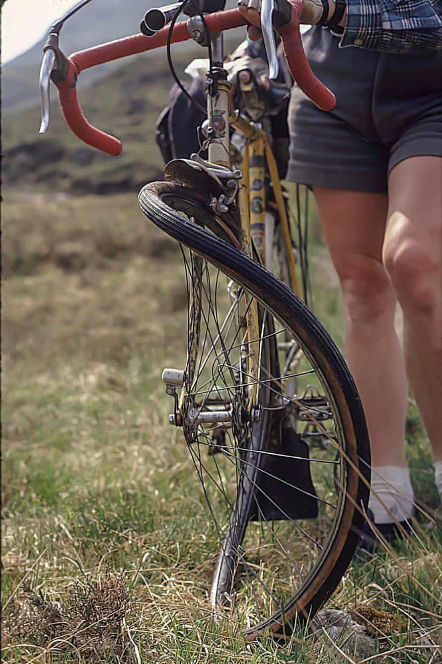 A cyclist shows examines his bent wheel. They were able to fix it and continue their journey