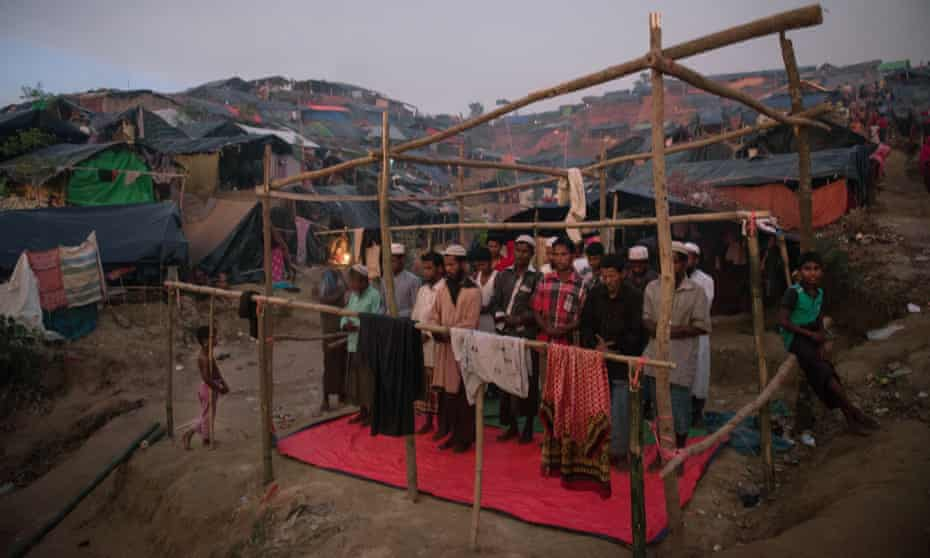 Rohingya Muslims say their evening prayers in a half completed structure at a refugee camp in Bangladesh.