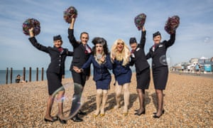 Drag queens Crystal Couture and Domini pose for a photo with British Airways ambassadors on the beach. The airline is a festival partner