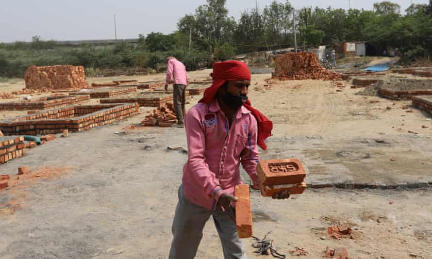 Workers construct new platforms to cremate bodies outside a crematorium, in New Delhi