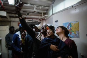 A migrant takes a selfie with an NGO volunteer before being transferred from a Dutch-flagged rescue vessel onto a Maltese armed forces ship.