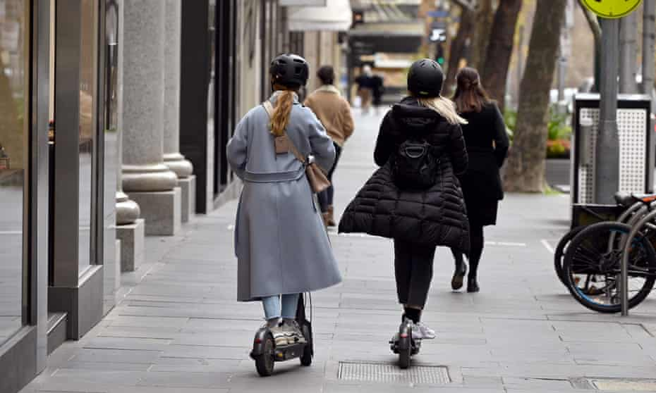 Two shoppers on e-scooters make their way down Collins Street in Melbourne
