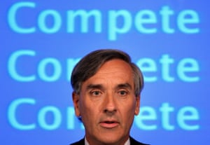 John Redwood, being banner saying 'compete compete copmete'