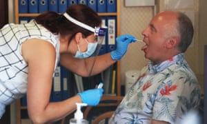 A care home worker in Whitley Bay, Tyneside, tests a resident with a swab