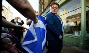 Tommy Sheppard campaigning during the election, with Niola Sturgeon (who is obscured in the picture, but who is signing the saltire.)<br>