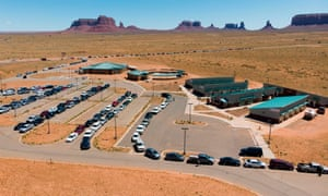 People line up in vehicles to collect water and supplies from a distribution point in Monument Valley at the Utah and Arizona border.