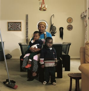 Victoria Cobokana, housekeeper, in her employer's dining room with her son Sifiso and daughter Onica, Johannesburg, June 1999. Victoria died of Aids on 13 December 1999, Sifiso died of Aids on 12 January 2000, Onica died of Aids in May 2000. From the series In the Time of Aids (detail), 1999